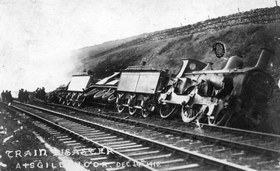 B&W photo showing two derailed locomtives, partially on their sides and the wreckage of the two leading carriages.