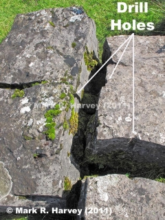 The same part-worked stone block from a different angle showing two grooves formed by a rock drill.