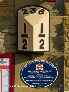 Settle Station Booking Office: wall-mounted milepost (236½) and NRHA plaque""